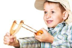 Criança que guarda o estilingue nas mãos foto de stock