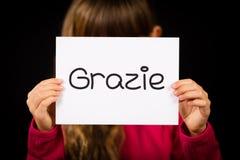 Criança que guarda o sinal com palavra italiana Grazie - obrigado imagens de stock royalty free