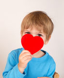 Criança que guarda um coração do dia de Valentim imagem de stock