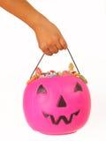 Criança que guarda uma abóbora plástica cor-de-rosa Foto de Stock