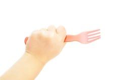 Criança que guarda uma forquilha plástica vermelha Imagem de Stock Royalty Free