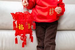 a criança que guarda uma lanterna e um bolso vermelho para o ano novo chinês, as palavras traduzidas à Inglês-fortuna na lanterna foto de stock royalty free