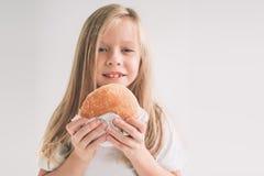 Criança que guarda uma parte de Hamburger A criança come o fast food alimento não útil E Menina isolada no branco foto de stock