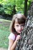 Criança que inclina-se de encontro a uma árvore de carvalho Imagem de Stock