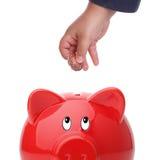 Criança que introduz a moeda em um banco piggy foto de stock royalty free