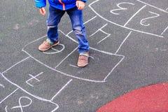 Criança que joga amarelinha no campo de jogos fora Foto de Stock