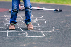 Criança que joga amarelinha no campo de jogos fora Imagens de Stock Royalty Free