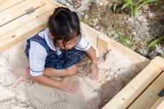 Criança que joga a areia na caixa de areia Foto de Stock