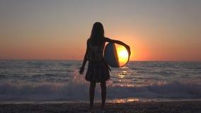 Criança que joga a bola de praia no por do sol, ondas de observação do mar da criança, opinião da menina no pôr do sol fotografia de stock royalty free