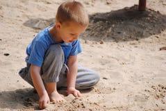 Criança que joga com areia Imagem de Stock