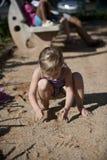 Criança que joga com a areia no campo de jogos Imagem de Stock