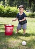 Criança que joga com as esferas no jardim Fotografia de Stock