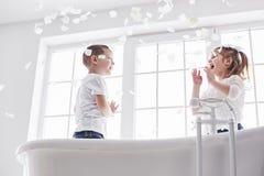 Criança que joga com as pétalas cor-de-rosa no banheiro da casa Menina e divertimento e alegria fawing do menino junto O conceito imagem de stock