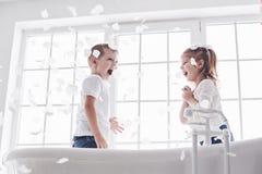 Criança que joga com as pétalas cor-de-rosa no banheiro da casa Menina e divertimento e alegria fawing do menino junto O conceito fotografia de stock
