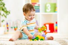 Criança que joga com blocos de apartamentos no jardim de infância foto de stock royalty free
