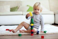 Criança que joga com blocos de madeira Fotografia de Stock