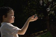Criança que joga com bolhas de sabão Fotografia de Stock Royalty Free