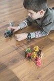 Criança que joga com brinquedos pequenos Fotografia de Stock