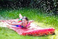 Criança que joga com corrediça de água do jardim Imagens de Stock Royalty Free
