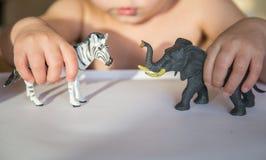 Criança que joga com duas figuras animais Os primeiros jogos de interpretação de personagem fotos de stock