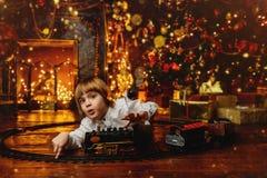 Criança que joga com estrada de ferro do brinquedo Fotos de Stock Royalty Free