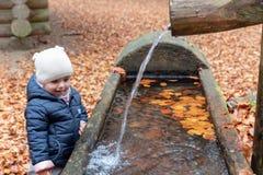 Criança que joga com a fonte de água em Forrest Playground foto de stock