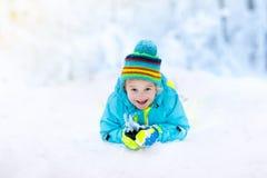 Criança que joga com neve no inverno Miúdos ao ar livre Foto de Stock