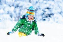 Criança que joga com neve no inverno Miúdos ao ar livre Imagens de Stock Royalty Free