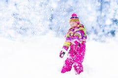 Criança que joga com neve no inverno Miúdos ao ar livre Imagem de Stock Royalty Free