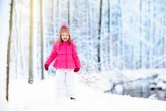 Criança que joga com neve no inverno Miúdos ao ar livre Foto de Stock Royalty Free