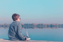 Criança que joga com o barco de navigação na luz bonita fotografia de stock