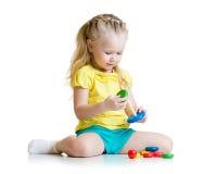 Criança que joga com o brinquedo da pirâmide da cor Fotografia de Stock Royalty Free