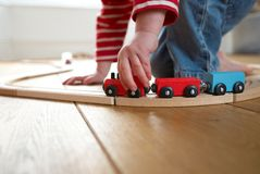 Criança que joga com o trem de madeira do brinquedo fotografia de stock