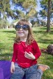Criança que joga com os óculos de sol adultos no parque Imagem de Stock Royalty Free