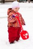 Criança que joga com a pá na neve fotografia de stock royalty free