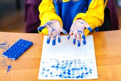 Criança que joga com pintura azul Fotos de Stock Royalty Free