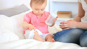 Criança que joga com sua garrafa de bebê video estoque