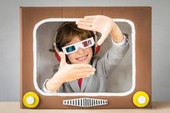 Criança que joga com tevê dos desenhos animados imagem de stock