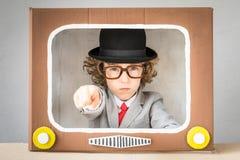 Criança que joga com tevê dos desenhos animados foto de stock