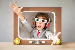 Criança que joga com tevê dos desenhos animados imagem de stock royalty free