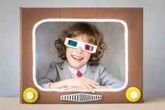 Criança que joga com tevê dos desenhos animados imagens de stock royalty free