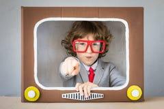 Criança que joga com tevê dos desenhos animados imagens de stock