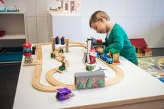 Criança que joga com trem do brinquedo Fotografia de Stock Royalty Free