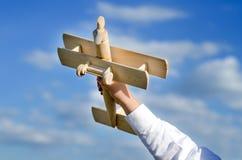 Criança que joga com um brinquedo de madeira do avião imagem de stock