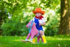 Criança que joga com um cavalo do brinquedo Imagens de Stock Royalty Free