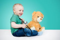 Criança que joga com urso de peluche imagens de stock