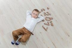 Criança que joga com véspera do ` s do ano novo do pão-de-espécie Foto de Stock