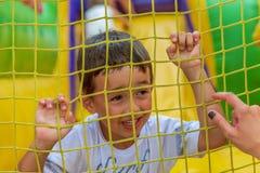 Criança que joga em torno do campo de jogos Imagens de Stock