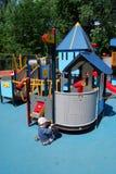 Criança que joga em um campo de jogos Fotografia de Stock