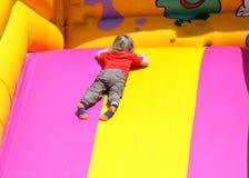 Criança que joga em uma corrediça. Imagens de Stock